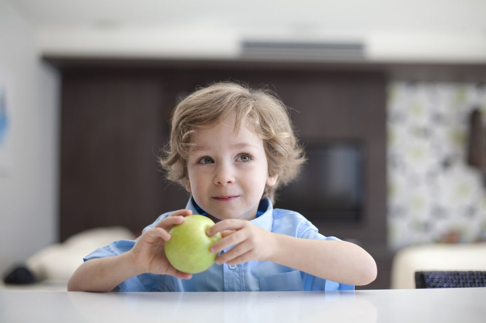 A young boy eating an apple.
