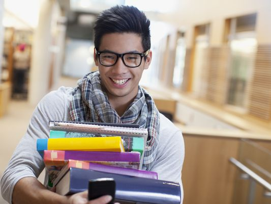 Student carrying a stack of textbooks