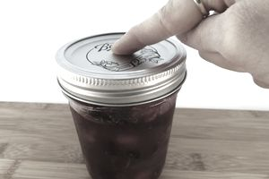 woman testing to see if canning jar is properly sealed