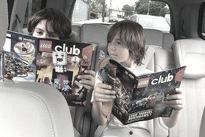 Two boys reading the free LEGO Life magazine.