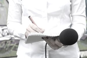Midsection Of Female Reporter Holding Microphone While Writing On Notepad