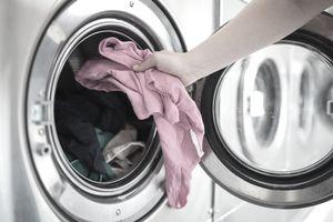 Woman putting shirt into washing machine