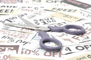 Open pair of scissors on top of a pile of coupons