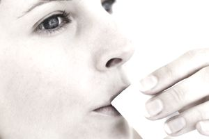 Close-up of a young woman sipping from a mouthwash cup