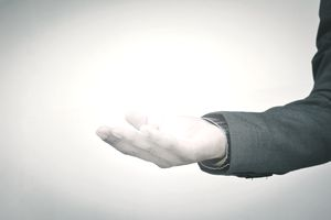 Digital Composite Image Of Hand Holding Light Bulb Against Gray Background