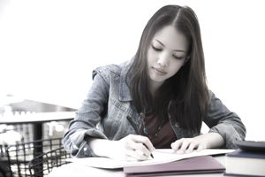 A young woman sitting at a desk writing in a notebook.