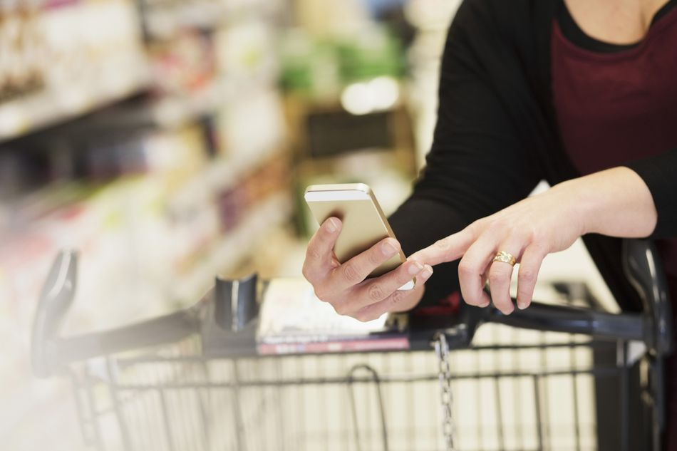 woman with smartphone shopping with cart