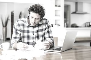 A man reviewing papers with a laptop