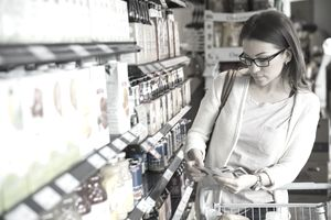 Woman shopping with coupons in market