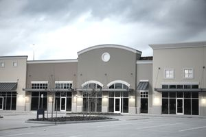 Empty new strip mall, shopping center buildings. Dusk, parking lot.