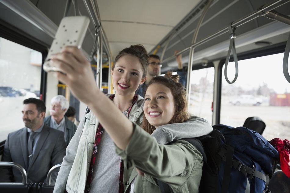 two women taking selfie on public bus