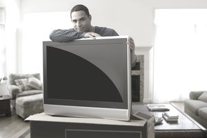 Hispanic man leaning on new television