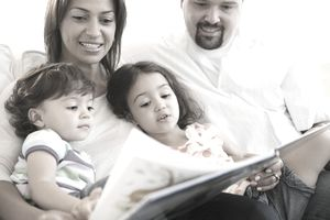 A family sitting on a couch reading a book together.