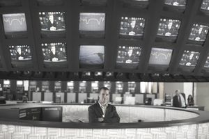 Man standing in a newsroom with TV monitors over his head