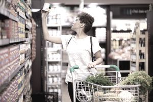 Woman compares brands and prices at grocery store