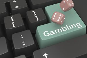 "Image of a Keyboard with the word ""Gambling"" in green and a pair of rolling dice"