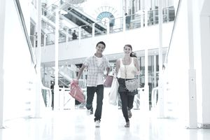 Smiling couple running and carrying shopping bags in mall